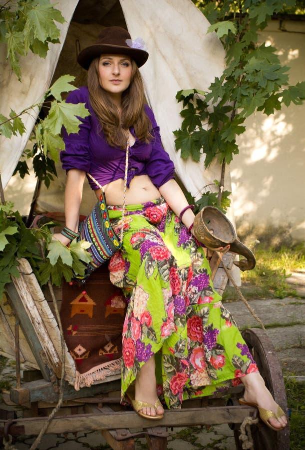 La fille dans le style de Bohème dans un chariot gitan dans le chapeau photo stock