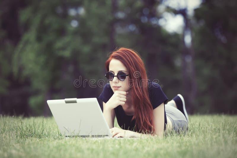 La fille dans le style indépendant vêtx avec l'ordinateur portable images stock