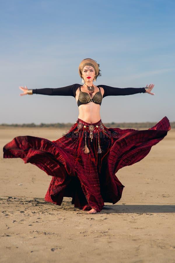La fille dans la longue robe rouge du style tribal américain photos stock
