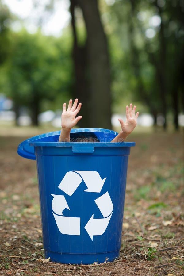 La fille dans la poubelle de rebut recyling de bleu ont l'amusement à l'intérieur Concept de protection de l'environnement Cadres images stock