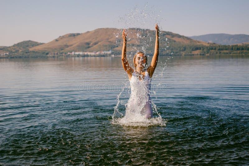 La fille dans la robe blanche se baigne pendant l'été de lac photographie stock libre de droits