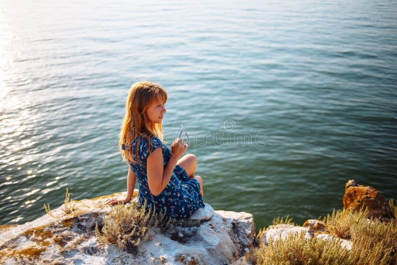 La fille dans la robe bleue sur la pierre s'assied par la mer images libres de droits