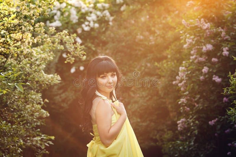 La fille dans la robe jaune est illuminée par belle lumière du soleil en parc sur le fond des arbustes fleurissants photos stock