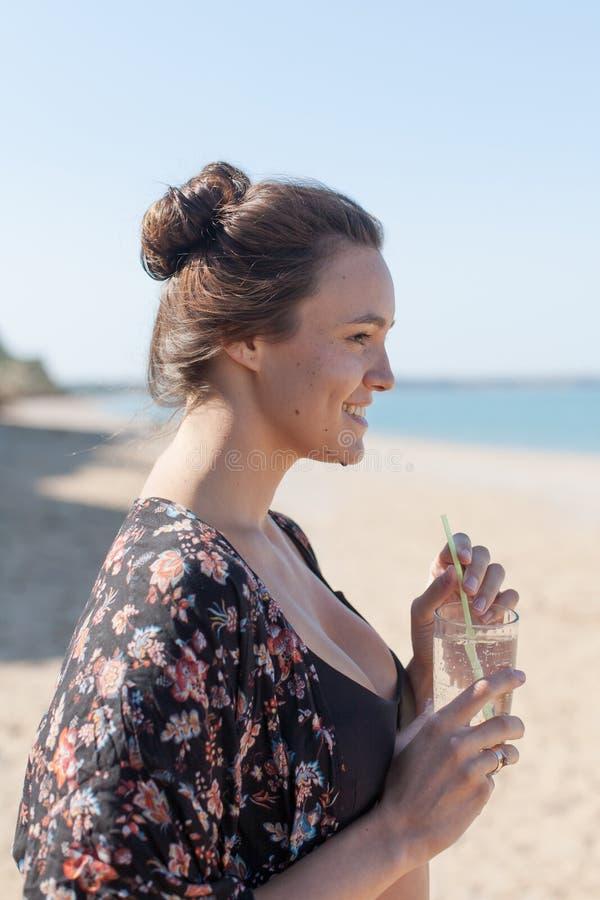 La fille dans la robe longue tient le verre de l'eau et de regard loin photographie stock libre de droits