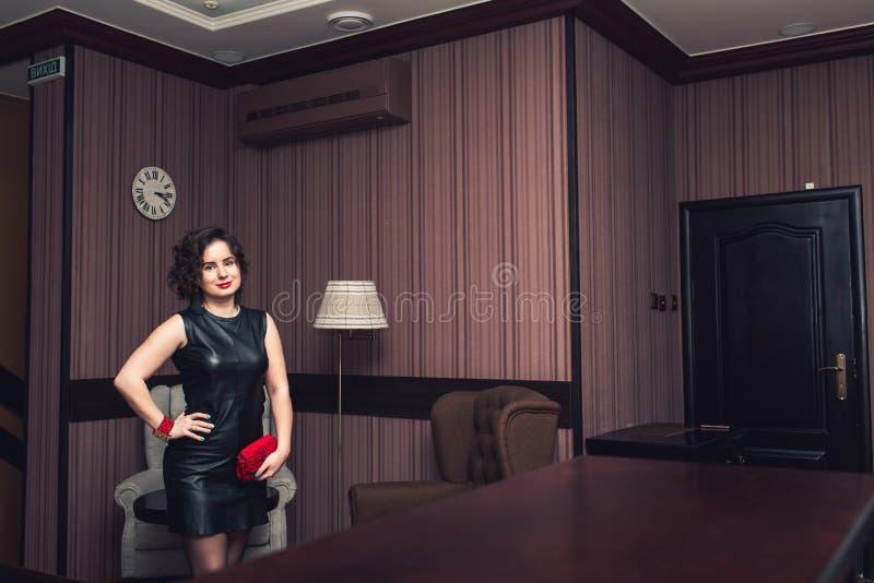 La fille dans la robe noire avec le bracelet rouge fait main, noircissent les boucles d'oreille et le sac tricotés photo stock