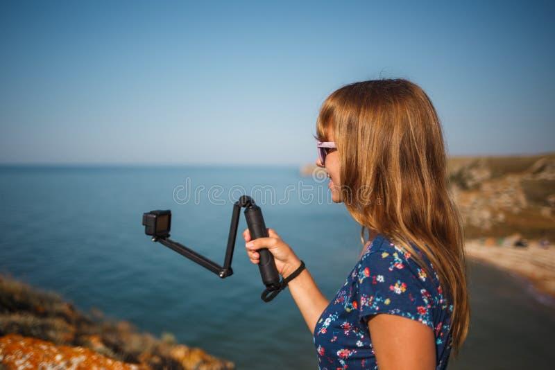 La fille dans la robe tire la vidéo sur la caméra d'action sur une plage sauvage photos libres de droits