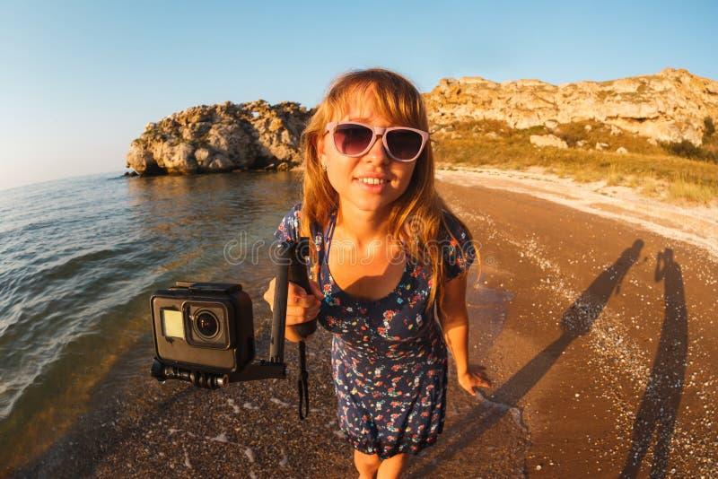 La fille dans la robe tire la vidéo sur la caméra d'action sur une plage sauvage image stock