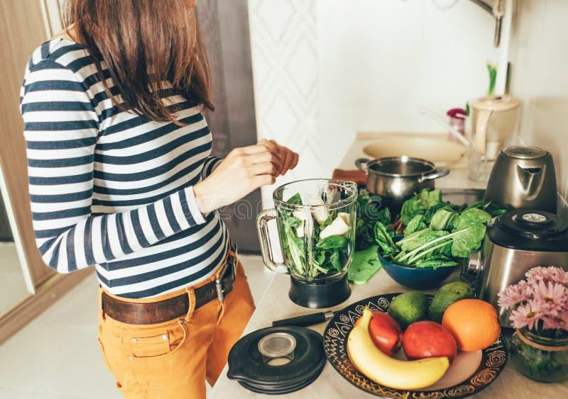 La fille dans sa cuisine prépare les ingrédients pour un smoothie photo stock