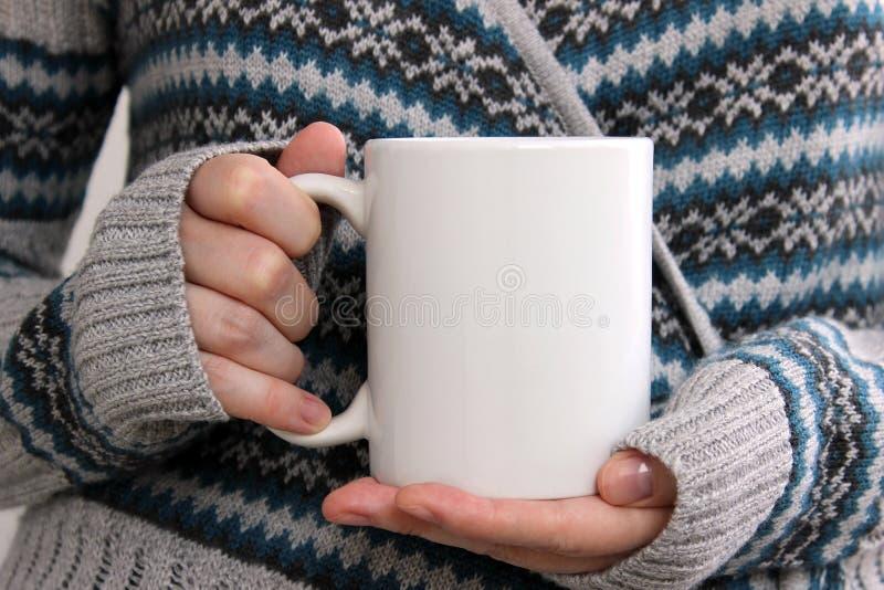 La fille dans un cardigan chaud tient la tasse blanche dans des mains image stock