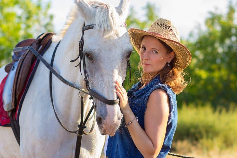 La fille dans un chapeau repasse un cheval blanc sur un museau image libre de droits