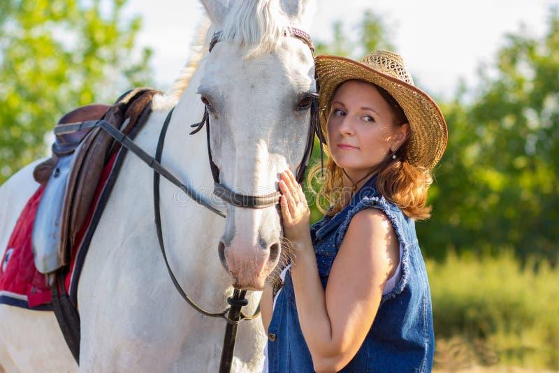 La fille dans un chapeau repasse un cheval blanc sur un museau photos libres de droits