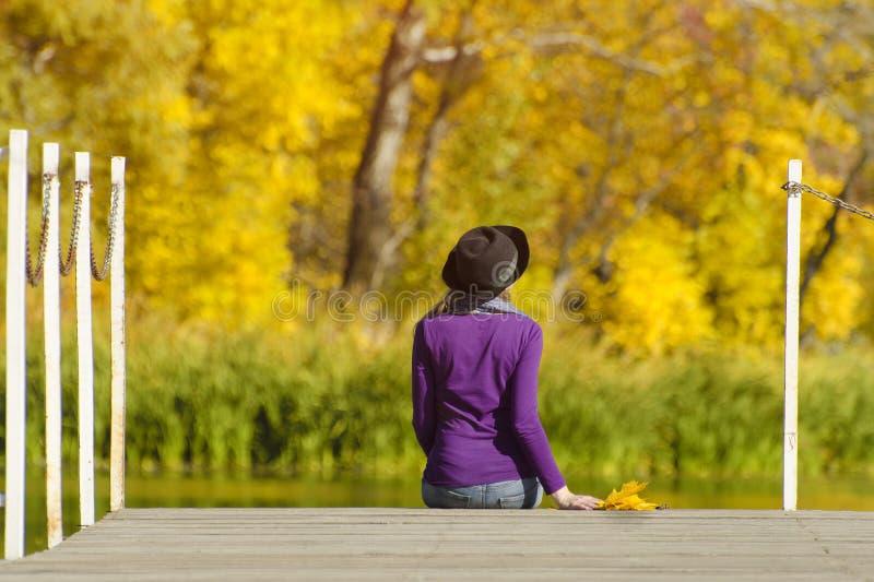 La fille dans un chapeau s'assied sur le dock et admire les couleurs de l'automne photos stock