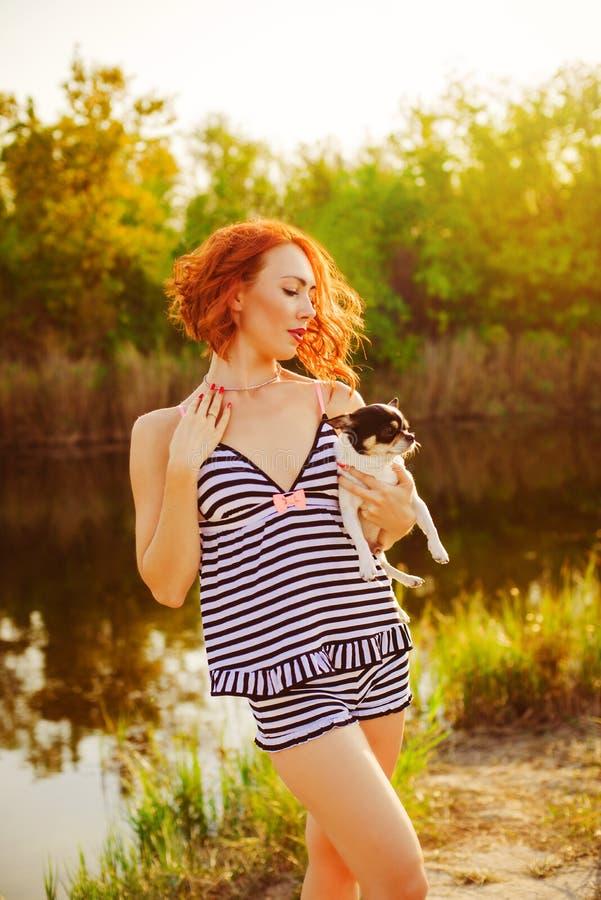 La fille dans un maillot de bain avec un petit chien au lac photo stock