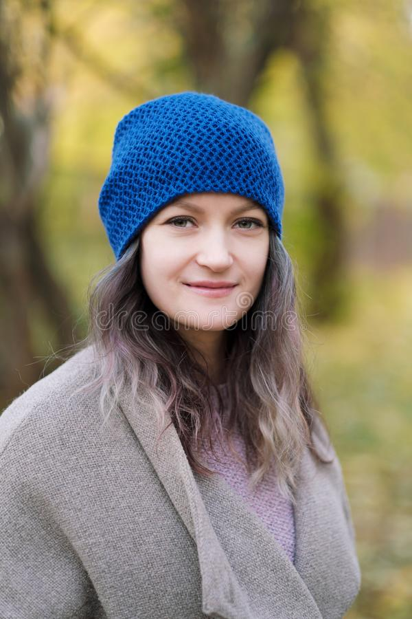 La fille dans un manteau et un chapeau bleu sur un fond des arbres d'automne et des feuilles d'érable images stock