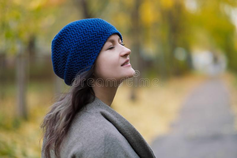 La fille dans un manteau et un chapeau bleu sur un fond des arbres d'automne et des feuilles d'érable image libre de droits