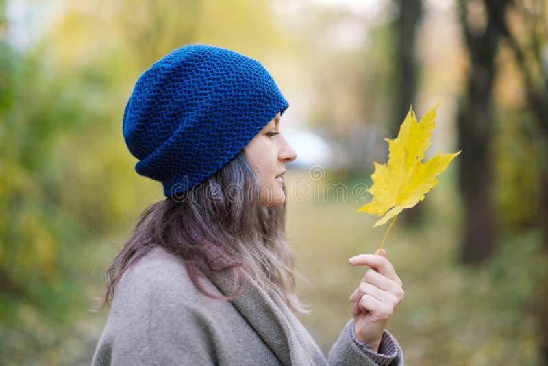La fille dans un manteau et un chapeau bleu sur un fond des arbres d'automne et des feuilles d'érable photos stock
