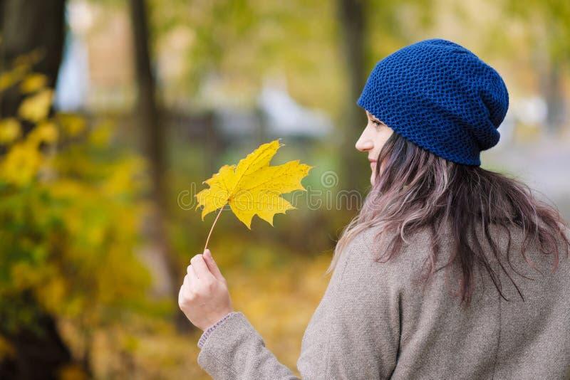 La fille dans un manteau et un chapeau bleu sur un fond des arbres d'automne et des feuilles d'érable photo stock