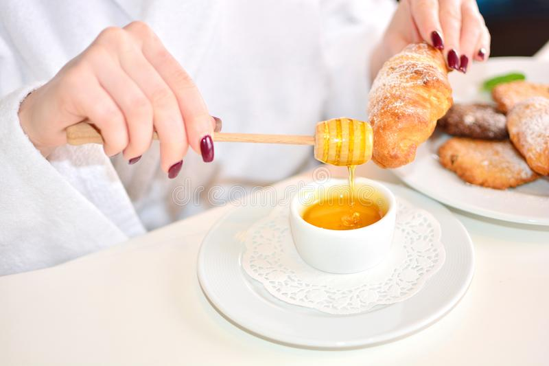 La fille dans un peignoir blanc mange les croissants à la maison avec du miel photographie stock