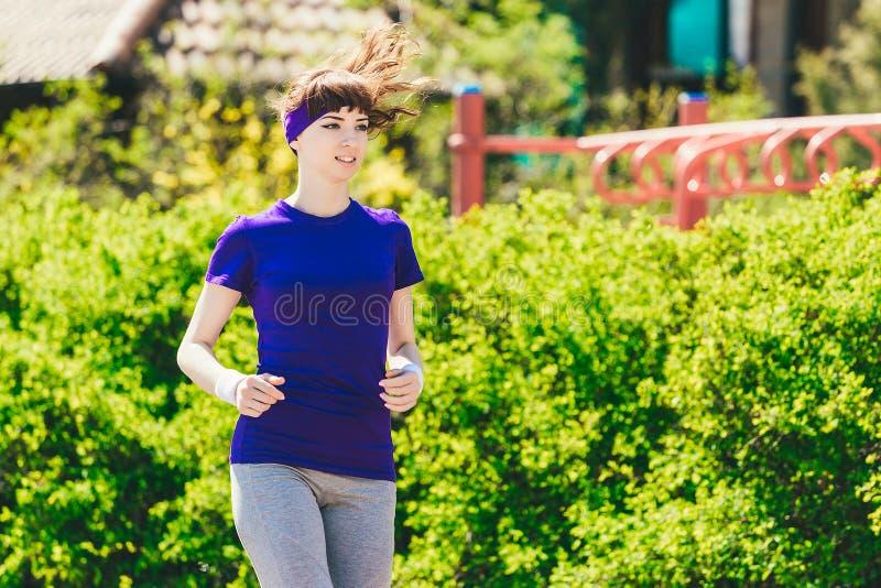 La fille dans un T-shirt bleu fait des sports en nature contre le contexte des buissons Jeune femme courant en stationnement photo libre de droits