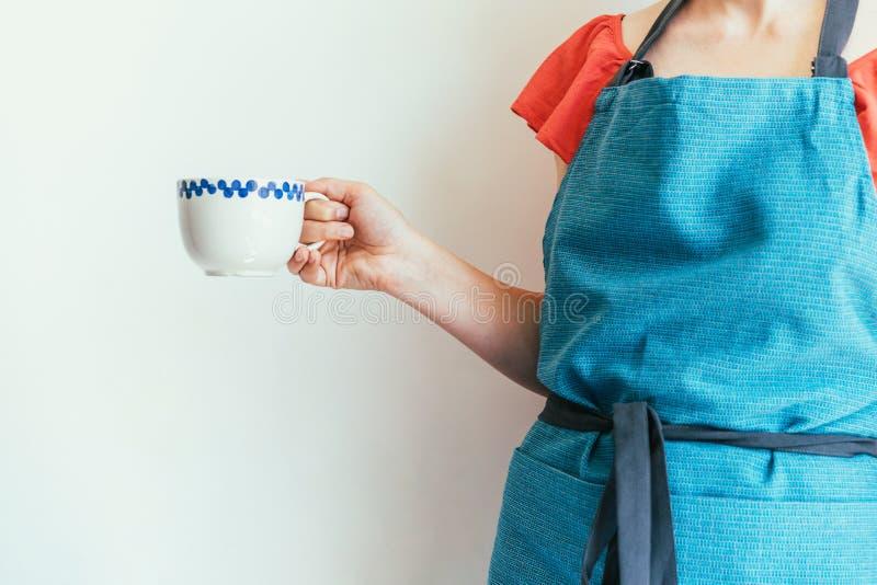 La fille dans un tablier bleu tient une grande tasse de café sur un fond blanc image stock