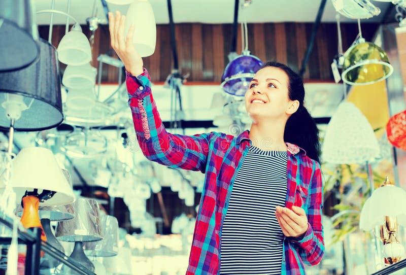La fille dans une boutique plus légère choisit la lampe élégante et moderne de lustre photo libre de droits
