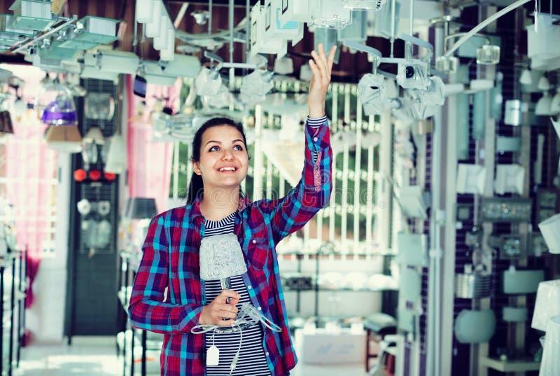 La fille dans une boutique plus légère choisit la lampe élégante et moderne de lustre image stock