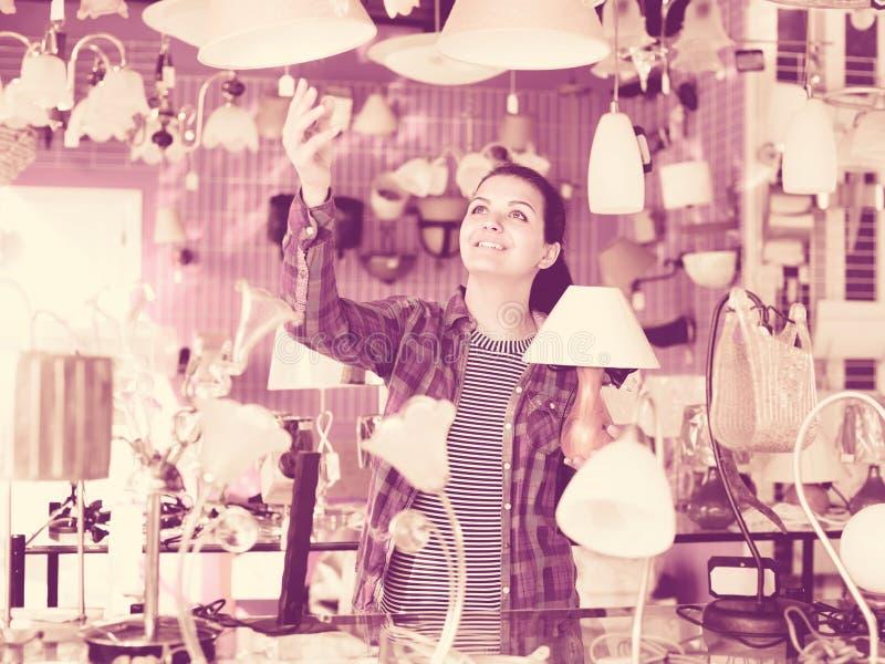 La fille dans une boutique plus légère choisit la lampe élégante et moderne de lustre image libre de droits