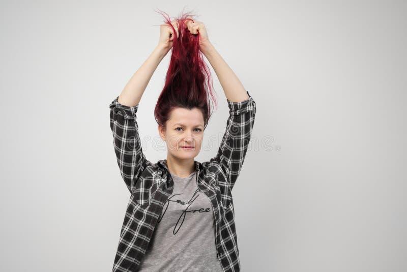 La fille dans une chemise grise de plaid sur un fond blanc avec les cheveux rouges teints image stock