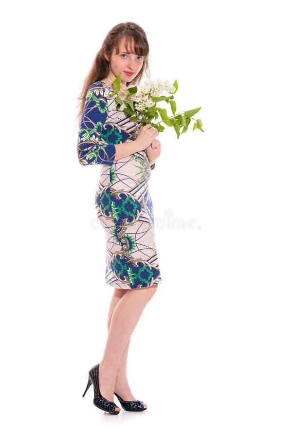 La fille dans une robe avec une branche du lilas blanc dans des ses mains Isolement sur un blanc photographie stock