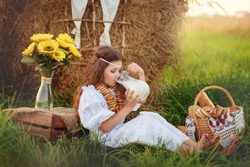 La fille dans une robe blanche boit du lait d'une cruche pendant l'été près de la meule de foin photographie stock libre de droits