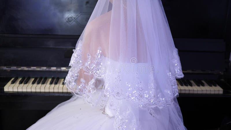 La fille dans une robe blanche joue le piano La jeune mariée exécute un morceau de musique sur le piano Industrie de la musique photo libre de droits