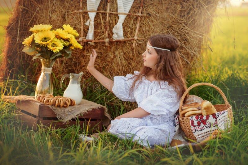 La fille dans une robe blanche s'assied sur l'herbe près de la meule de foin pendant l'été photo stock