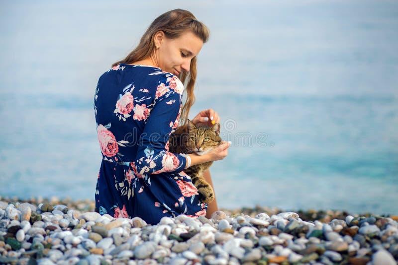 La fille dans une robe bleue repose un dos sur la banque de la mer Méditerranée et repasse un chat photos libres de droits