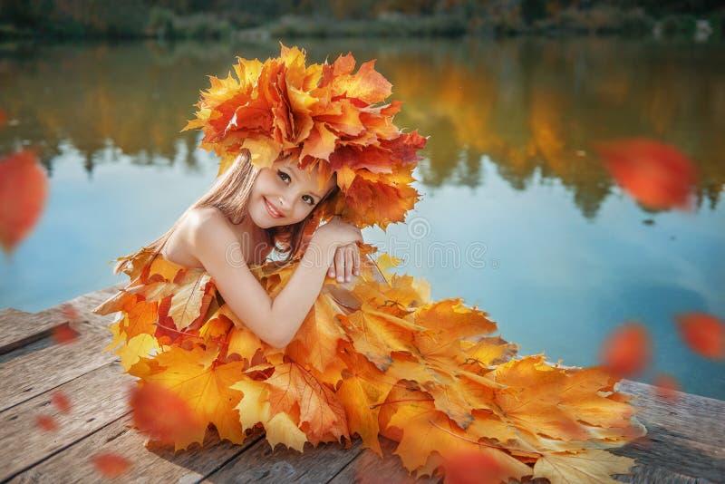 La fille dans une robe d'automne des feuilles sur le rivage du lac images libres de droits