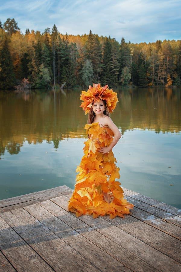 La fille dans une robe d'automne des feuilles sur le rivage du lac photos stock