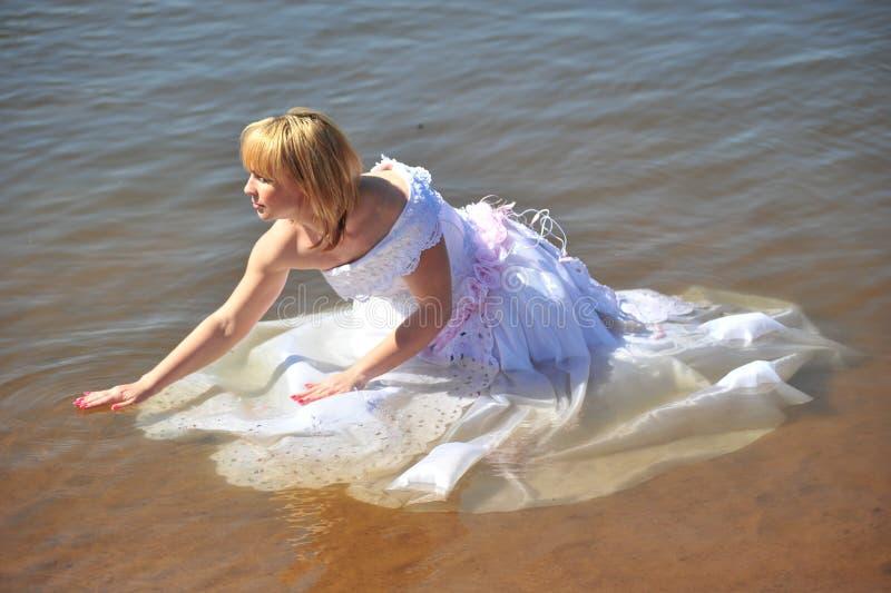 La fille dans une robe de mariage dans l'eau image libre de droits