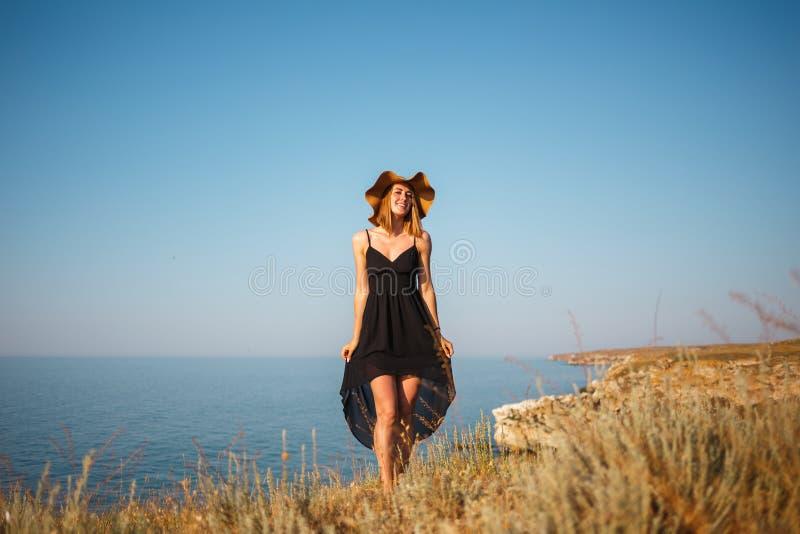 La fille dans une robe et un chapeau noirs sur une plage rocheuse regarde la mer images stock