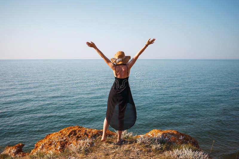 La fille dans une robe et un chapeau noirs sur une plage rocheuse regarde la mer photos stock