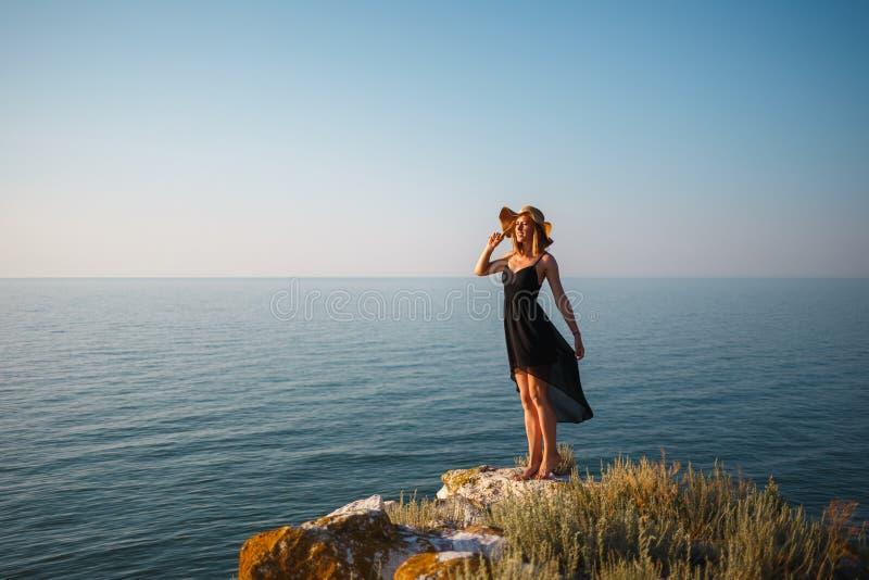 La fille dans une robe et un chapeau noirs sur une plage rocheuse regarde la mer photos libres de droits