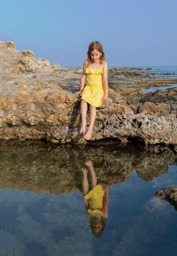 La fille dans une robe jaune sur une roche sur une plage de mer est reflétée dans l'eau bleue photographie stock libre de droits