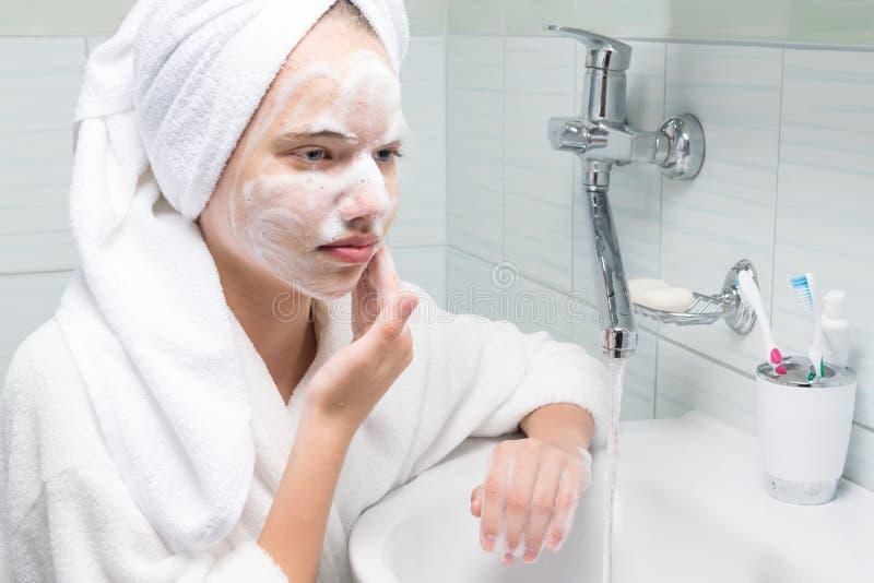 La fille dans une robe longue blanche se lave le visage avec des lessives de savon dans la salle de bains images libres de droits