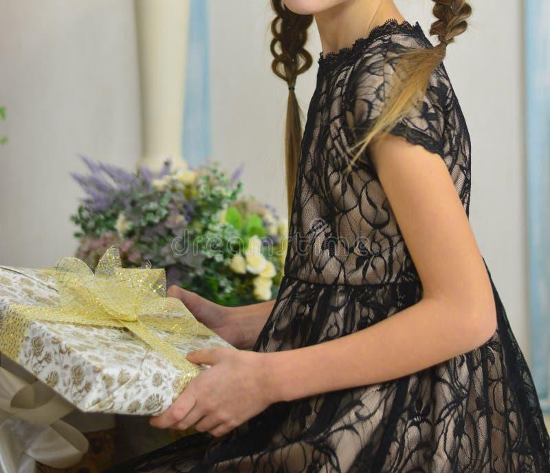 La fille dans une robe noire tient un cadeau ouvrez les cadeaux d'anniversaire photos libres de droits