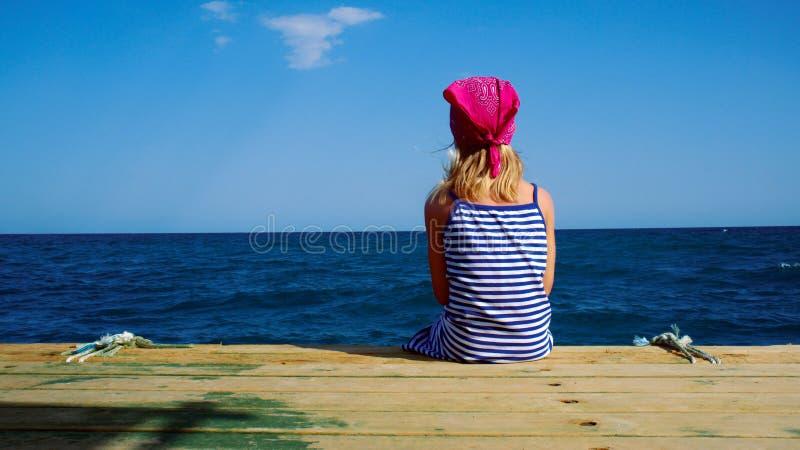 La fille dans une robe rayée regarde la mer bleue photographie stock libre de droits