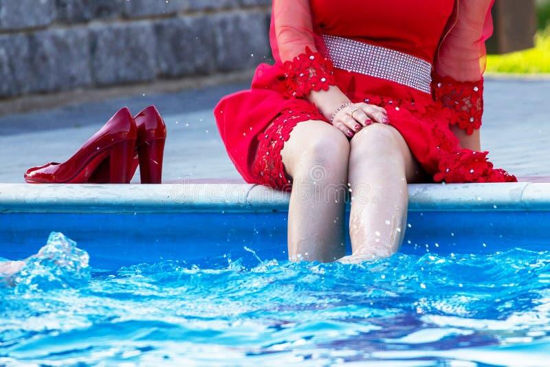 La fille dans une robe rouge s'est assise par la piscine et a plongé ses jambes dans le water_ photos stock