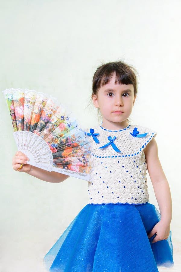 La fille dans une robe tient une fan images stock