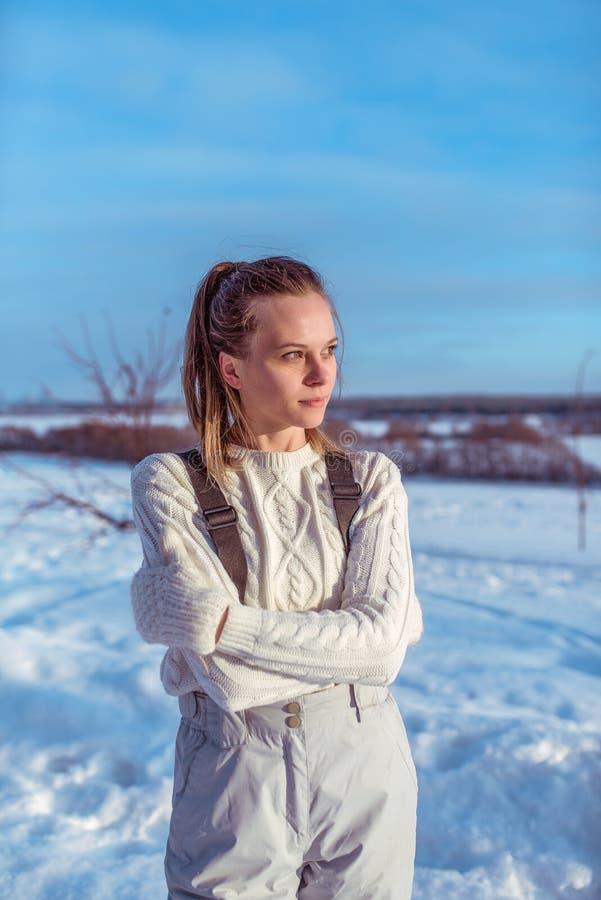 La fille dans une salopette blanche en hiver dehors, fond est des dérives de neige, examinant la distance, un chandail chaud et l photo stock