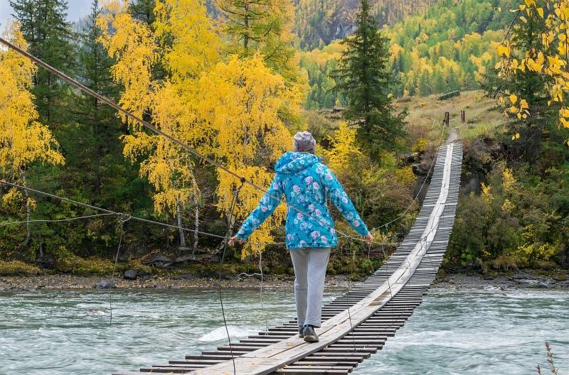 La fille dans une veste chaude va sur un pont suspendu en bois de l'autre côté de la rivière de turquoise Paysage W de montagne d image stock