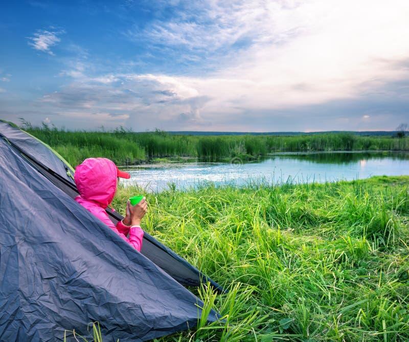 La fille dans la veste rose s'assied à la sortie de la tente avec la tasse et regarde image libre de droits