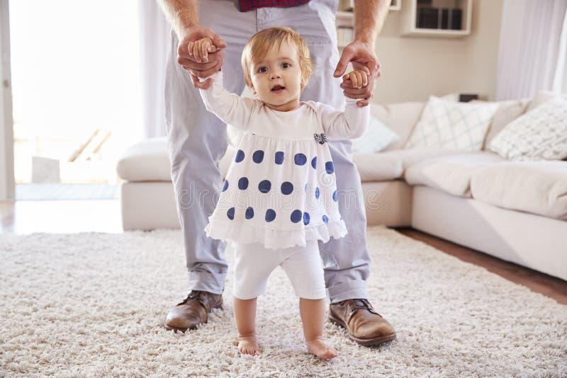 La fille de aide de père apprennent à marcher dans le salon photo stock