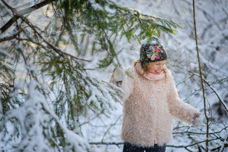 La fille de 8-9 ans pour secouer sur elle-même la neige d'un sapin photo stock